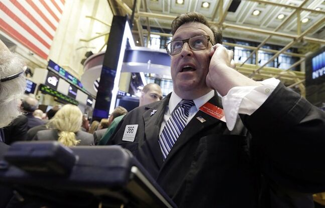 FILE - In this July 16, 2014 file photo, trader Benedict Willis uses his moblie phone as he works on the floor of the New York Stock Exchange. Stocks are pricier, tensions between Russia and the West are mounting, and Israel has rolled into Gaza to stop a deadly air war. And yet investors shrug it all off and keep pushing the market higher. (AP Photo/Richard Drew, File)