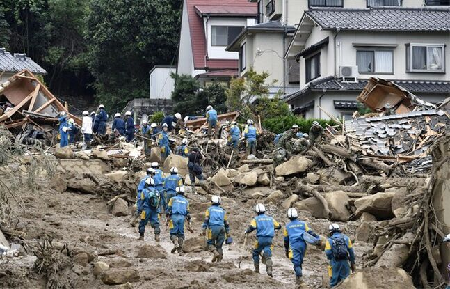 Rescue workers search for survivors after a massive landslide swept through residential areas in Hiroshima, western Japan, Wednesday, Aug. 20, 2014. Rain-sodden slopes collapsed in torrents of mud, rock and debris early Wednesday in the outskirts of Hiroshima, killing at least 36 people, police said. (AP Photo/Kyodo News) JAPAN OUT, MANDATORY CREDIT