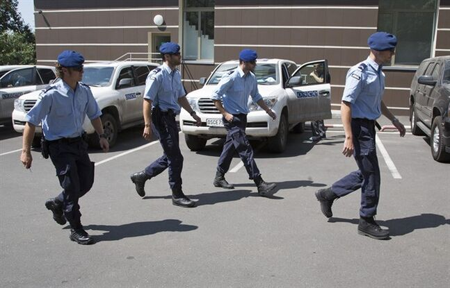 Dutch policemen walk to their cars in the city of Donetsk, eastern Ukraine Sunday, July 27, 2014. A team of international police officers that had been due to visit the site of the Malaysian plane disaster in eastern Ukraine cancelled the trip Sunday after receiving reports of fighting in the area. Alexander Hug, the deputy head of a monitoring team from the OSCE in Europe, said it would be too dangerous for the unarmed mission to travel to the site from its current location in the rebel-held city of Donetsk. (AP Photo/Dmitry Lovetsky)