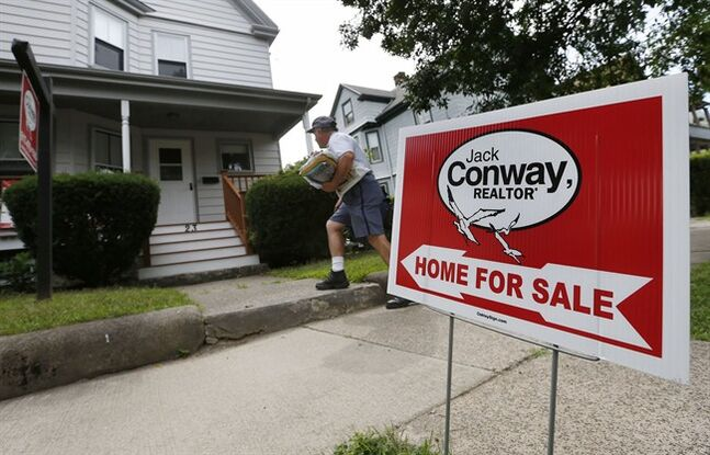 A mailman delivers mail to a house for sale in Quincy, Mass. on July 10, 2014. THE CANADIAN PRESS/AP, Michael Dwyer