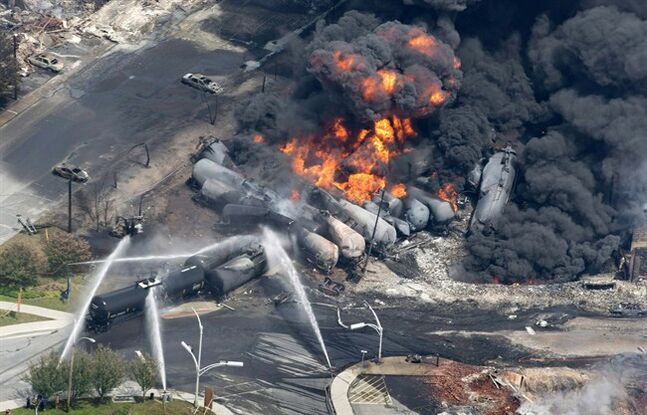 Smoke rises from railway cars that were carrying crude oil after derailing in downtown Lac-Mégantic, Que., July 6, 2013.