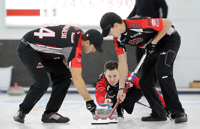 Derek Samagalski (left) and Brendan Taylor sweep skip Rob Fowler's rock during the Brandon Men's Bonspiel.