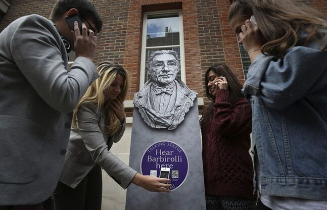 People listen to a talking statue on their phones at the launch of Talking Statues in central London, Tuesday Aug. 19, 2014. Statues of some three dozen historical and fictional characters in London and Manchester are coming to life thanks to a new interactive project that gives them a voice to tell their stories. Passers-by can swipe their smartphones on a tag or type in a web address to get an instant call from the characters depicted. Actors including Patrick Stewart and Downton Abbey's Hugh Bonneville perform the monologues, which lasts a few minutes each. (AP Photo/PA, Philip Toscano) UNITED KINGDOM OUT NO SALES NO ARCHIVE