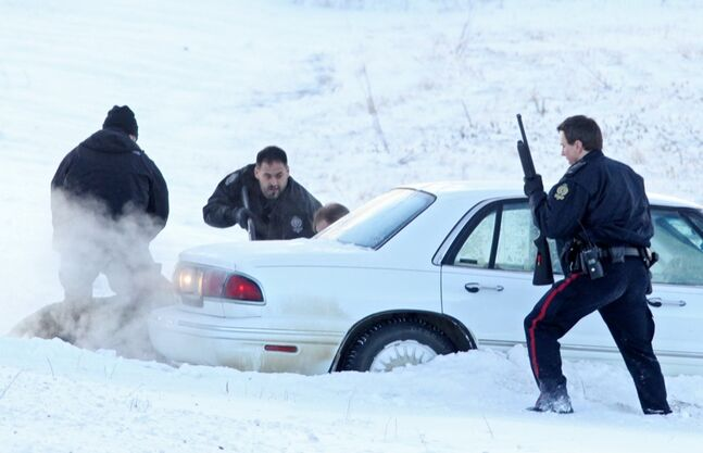 With guns drawn Brandon Police Service members take down a suspect (obstructed by the vehicle) in a string of car robberies after a stolen Buick LeSabre hit the ditch on Highway 110 east of Brandon after a police pursuit on Tuesday morning. Two suspects, a man and a woman, were taken into custody.