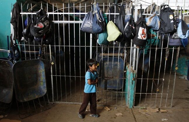 In this Jan. 28, 2014 photo, a boy walks under backpacks that belong to children who work as porters at the El Abasto market in Santa Cruz, Bolivia. A 2008 study done by the International Labor Organization and Bolivian government found that 850,000 children ages 5 to 17 were working in Bolivia, roughly half in the countryside and half in the cities. (AP Photo/Juan Karita)