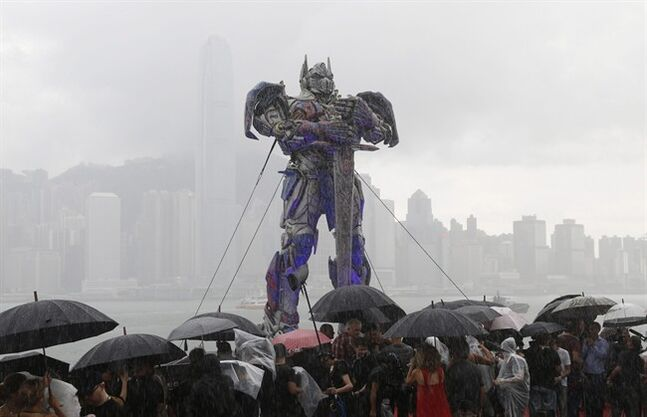 People duck and hide themselves under umbrellas as a giant figure of Optimus Prime from the movie