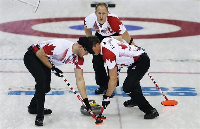 Canada's Brad Jacobs, back, watches as Ryan Harnden, left, and E.J. Harnden, right, sweep the ice during the men's curling match against the United States at the 2014 Winter Olympics, Sunday, Feb. 16, 2014, in Sochi, Russia. (AP Photo/Wong Maye-E)