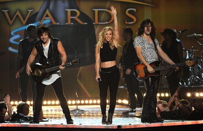 FILE - In this April 6, 2014 file photo, Neil Perry, left, Kimberly Perry and Reid Perry, of the musical group The Band Perry, perform at the 49th annual Academy of Country Music Awards at the MGM Grand Garden Arena, in Las Vegas. The Band Perry's lead singer Kimberly Perry has married Texas Rangers baseball player J.P. Arencibia near her family's home in Greeneville, Tenn. A publicist for the band confirmed the wedding occurred Thursday, June 12, 2014. (Photo by Chris Pizzello/Invision/AP, file)