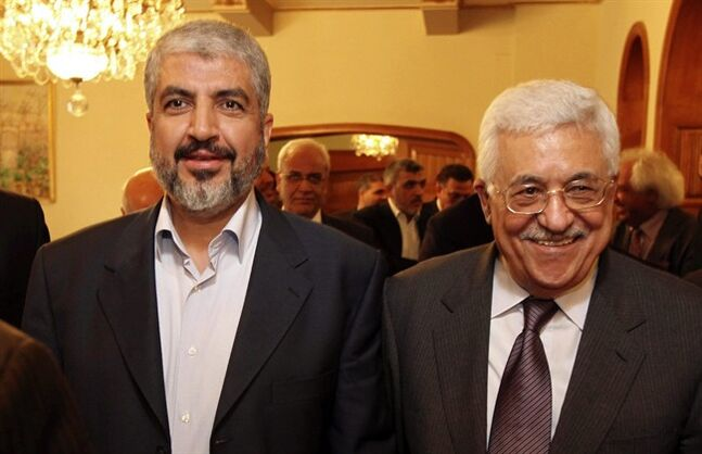 FILE - In this file photo provided on Nov. 24, 2011, by the office of Khaled Mashaal, Palestinian Hamas leader Khaled Mashaal, left, and Palestinian President Mahmoud Abbas are seen together during their meeting in Cairo, Egypt. A negotiator said Monday, May 26, 2014, that he expects a Palestinian unity government to be announced later this week in what would be a first significant step toward ending the crippling rift between Hamas and Fatah. (AP Photo/Office of Khaled Meshaal, File)