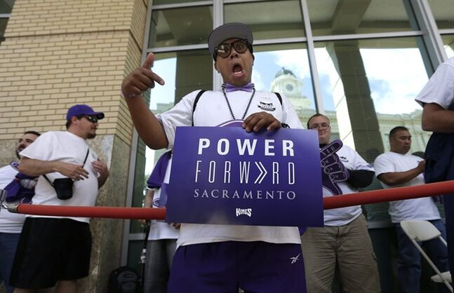 Sacramento Kings fan J.R. Basa waits in line with dozens of other Kings fans to enter City Hall, where the council is scheduled to vote on a $477 million downtown arena for the Kings, in Sacramento, Calif., Tuesday, May 20, 2014. The city would be responsible for a $223 million subsidy, much of it financed through a bond backed by the city's parking revenue. If approved, the Kings are scheduled to break ground this summer and open in time for the 2016-17 season. (AP Photo/Rich Pedroncelli)