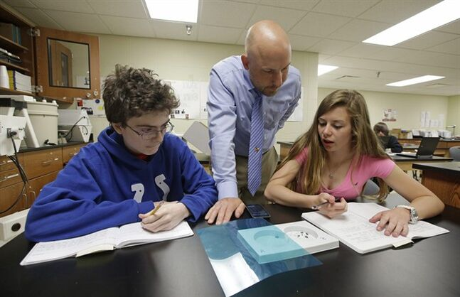 Matthew Davis, left, and Shannon Newerth study the habits of bugs with teacher Chris Kaufman during a Plant and Soil Science class at Beech Grove High School Wednesday, April 30, 2014, in Indianapolis. High school agriculture programs sprouting across the nation's Corn Belt are teaching teenagers, many of them in urban environments, that careers in the field often have nothing to do with cows and plows. (AP Photo/Darron Cummings)