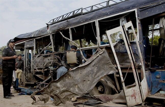 Pakistani police officers examine a damaged bus at the site of a bombing in Karachi, Pakistan, Thursday, Feb. 13, 2014. A bomb attack killed at least several police officers and wounded dozens others in Pakistan's southern city of Karachi on Thursday. (AP Photo/Shakil Adil)