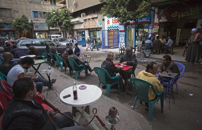 In this March 19, 2014, photo, Egyptians sit in an outdoor cafe next to the Zawya cinema off the packed streets of downtown Cairo. Zawya, built into an annex of a onetime movie palace-turned multiplex, sells several dozen tickets per day, its box office says, while special premier screenings have filled it beyond capacity. (AP Photo/Khalil Hamra)