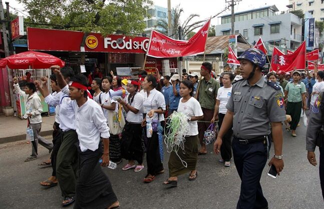 Myanmar police provide security while Myanmar blue collar workers shout slogans as they march to protest near the South Korean Embassy of Korea Thursday, July 17, 2014, in Yangon, Myanmar. About 700 workers who lost their jobs as a South Korean owner of a footwear factory abruptly shut the factory down four-weeks ago, marched to the South Korean embassy in Yangon shouting slogans, demanding wages and compensation. (AP Photo/Khin Maung Win)