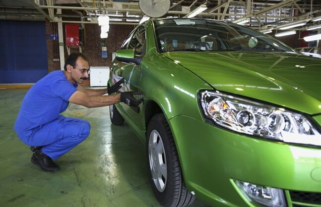 Iranian car worker Iraj Zarouri inspects a car before it's exported to Russia for the first time since 2009, at the state-run Iran-Khodro automobile manufacturing plant near Tehran, Iran, Sunday, June 29, 2014. Iran began exporting automobiles to Russia for the first time in five years on Sunday, after meeting upgraded emission standards, the country's largest auto manufacturer said. (AP Photo/Vahid Salemi)