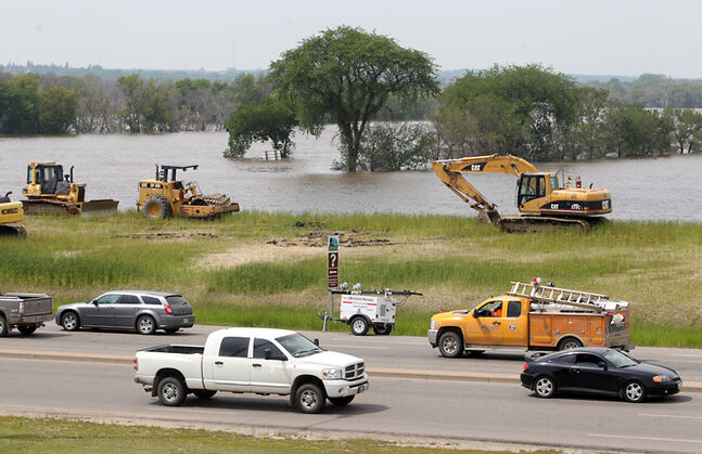 Assiniboine River floodwaters lap up against the dike along 18th Street near Kirkcaldy Avenue on Thursday. City officials are confident the dike will withstand the river's second crest, which is expected today through Sunday.