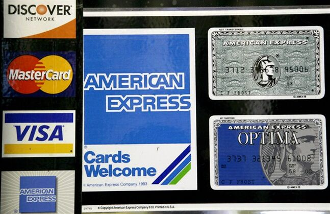 FILE - In this Sept. 5, 2007 file photo, credit card decals adorn a store window in the Hollywood section of Los Angeles. The Federal Reserve reports on consumer borrowing data for June 2014 on Thursday, Aug. 7, 2014. (AP Photo/Nick Ut, File)