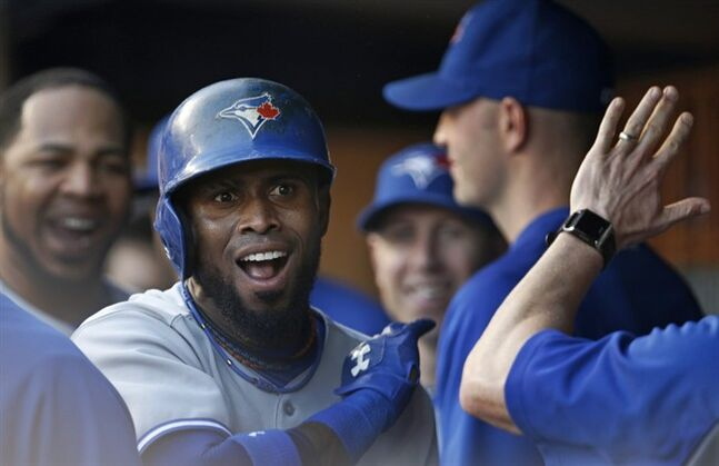 Toronto Blue Jays Jose Reyes reacts in the dugout as teammates greet him after he hit a first-inning lead-off solo home run off New York Yankees starting pitcher Masahiro Tanaka in a baseball game at Yankee Stadium in New York, Tuesday, June 17, 2014. (AP Photo/Kathy Willens)