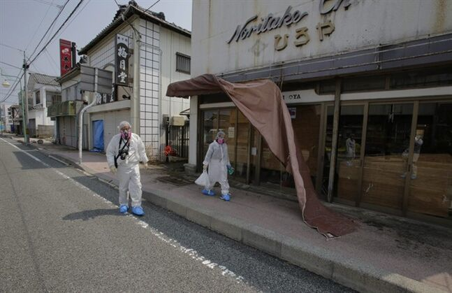 "In this photo taken Thursday, April 17, 2014, Kazuhiro Onuki, left, and his wife, Michiko, wearing white protective gears and filtered masks, walk in front of their ceramic and craft shop home in Tomioka, Fukushima Prefecture, northeastern Japan. ""The prime minister says the accident is under control, but we feel the thing could explode the next minute,"" said Michiko. It's difficult to imagine ever living again in Tomioka, a ghost town about 10 kilometers (6 miles) from the former Fukushima Dai-ichi nuclear plant. (AP Photo/Shizuo Kambayashi)"