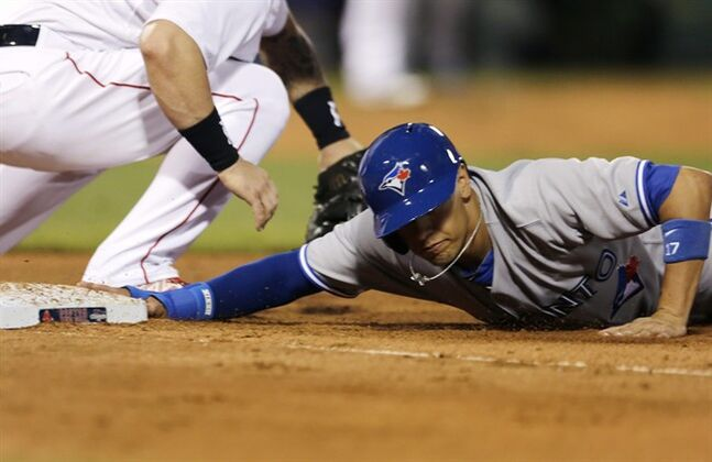 Toronto Blue Jays' Ryan Goins dives safely back to first base on a pick-off attempt by Boston Red Sox starting pitcher Clay Buchholz during the fourth inning of a baseball game at Fenway Park in Boston, Monday, July 28, 2014. (AP Photo/)