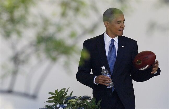 FILE - In this Thursday, May 21, 2009, file photo, President Barack Obama plays with a football as he walks back to the Oval Office of the White House in Washington. Concerned that too little is known about the effects of head injuries in young athletes, President Barack Obama is bringing representatives of professional sports leagues, coaches, parents, youth sports players, researchers and others to the White House Thursday, May 29, 2014, to help educate the public about youth sports concussions. (AP Photo/Charles Dharapak, File)