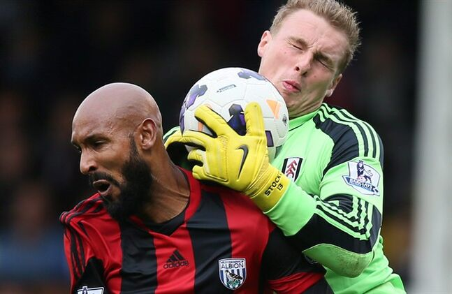 Fulham's goalkeeper David Stockdale, right, holds onto the ball as he clashes with West Brom's Nicolas Anelka during their English Premier League soccer match between Fulham and West Bromwich Albion at Fulham's Craven Cottage stadium in London Saturday, Sept. 14 2013. THE CANADIAN PRESS/AP/Alastair Grant