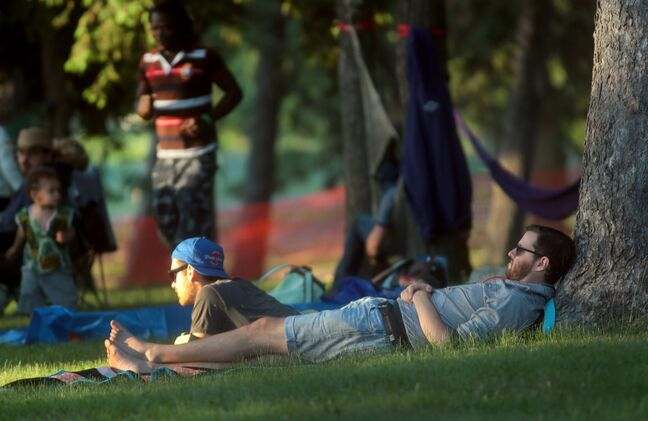 A pair of folk festival goers relax amongst the trees during Friday evening's performances at the Brandon Folk Music and Arts Festival.