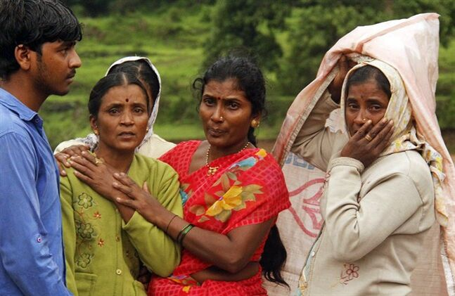 Villagers console each other as they watch a rescue operation at the site of a landslide in Malin village, in the western Indian state of Maharashtra, Wednesday, July 30, 2014. Torrential rains triggered a massive landslide that buried a remote village in western India on Wednesday, killing more than a dozen people as it swept away scores of houses and possibly trapping many more people under debris, officials said. (AP Photo)