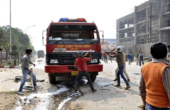 People vandalize a firetruck on the first day of a two day strike in Noida, a suburb of New Delhi, India, Wednesday, Feb. 20, 2013. Sporadic violence has broken out in India at the beginning of a two-day strike by labor unions protesting rising prices and government policies to open the economy. (AP Photo)