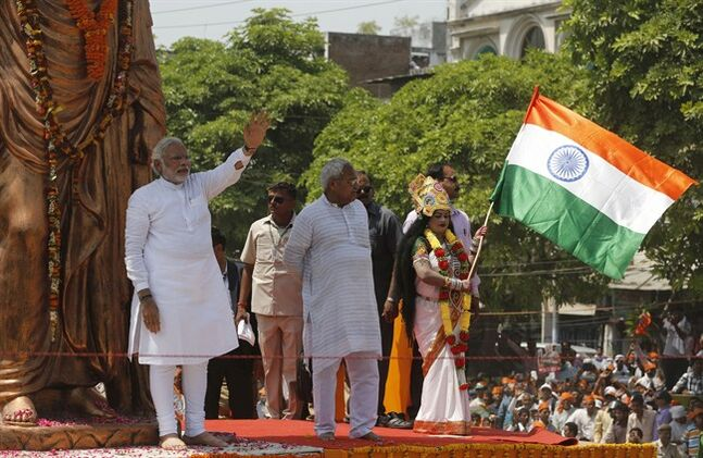 India's main opposition Bharatiya Janata Party's (BJP) Prime ministerial candidate Narendra Modi waves to supporters as a woman dressed as Mother india waves the national flag in Varanasi, in the northern Indian state of Uttar Pradesh, Thursday, April 24, 2014. During his campaign, Modi has not played up his party's Hindu agenda, but experts say his decision to run in this holy city is meant to send a clear message to all voters about his commitment to the BJP's brand of religious nationalism, which emphasizes India's Hindu identity. (AP Photo/Rajesh Kumar Singh)