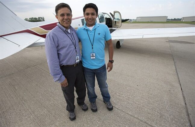 File - In this June 19, 2014 file photo, Babar Suleman, left, and son Haris Suleman, 17, stand next to their plane at an airport in Greenwood, Ind., before taking off for an around-the-world flight. Officials in American Samoa on Monday, Aug. 4, 2014, recovered a personal locator beacon registered to the Sulemans, who crashed off the U.S. territory last month as they attempted to fly around the world. Haris Suleman died in the July 22 crash and his father, Babar Suleman, remains missing. (AP Photo/The Indianapolis Star, Robert Scheer, File)