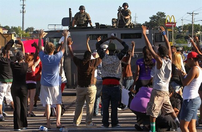 Protesters raise their hands in front of police atop an armored vehicle in Ferguson, Mo. on Wednesday, Aug. 13, 2014. On Saturday, Aug. 9, 2014, a white police officer fatally shot Michael Brown, an unarmed black teenager, in the St. Louis suburb. (AP Photo/St. Louis Post-Dispatch, J.B. Forbes)