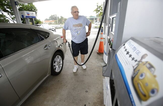 In this Wednesday, June 4, 2014 photo, Marty Mascio, of Pembroke Pines, Fla., pumps gasoline into his car at a Chevron gasoline station in Pembroke Pines, Fla. The Labor Department reports on U.S. consumer prices in May on Tuesday, June 17, 2014. (AP Photo/Wilfredo Lee)