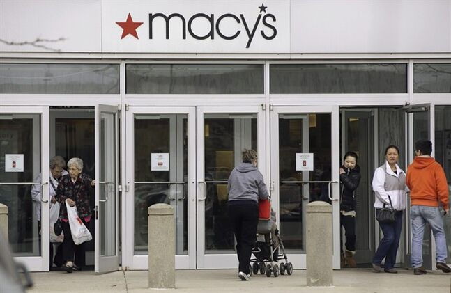 FILE - In this April 29, 2014 file photo, shoppers enter and leave a Macy's department store in Braintree, Mass. Macy's Inc. reports quarterly financial results before the market opens Wednesday, Aug. 13, 2014. (AP Photo/Stephan Savoia)