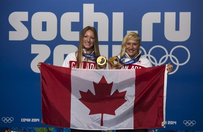 Kaillie Humphries, right, and Heather Moyse, bobsleigh gold medalists, pose with the Canadian flag as they are introduced as the flag bearers for the closing ceremonies at the Sochi Winter Olympics Sunday, February 23, 2014 in Sochi. THE CANADIAN PRESS/Paul Chiasson