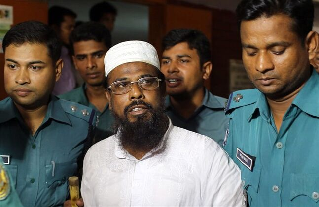 FILE - In this Monday, June 16, 2014 file photo, Mufti Abdul Hannan, center, leader of banned radical group Harkatul Jihad al Islami, stands at a court in Dhaka, Bangladesh. The court on Monday, June 23 sentenced eight people, including the top leader of the banned Islamist group, to death for their roles in a bombing at a New Year's celebration concert 13 years ago. (AP Photo/A.M. Ahad, File)