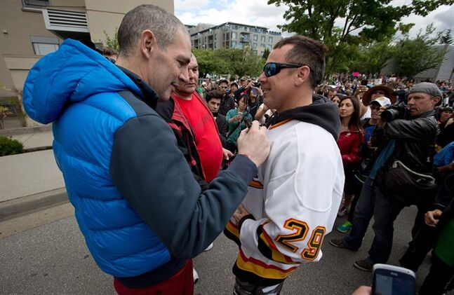 Former Vancouver Canucks' enforcer Gino Odjick, left, autographs a jersey for a fan after greeting hundreds of people gathered to support him outside Vancouver General Hospital in Vancouver, on Sunday June 29, 2014. THE CANADIAN PRESS/Darryl Dyck