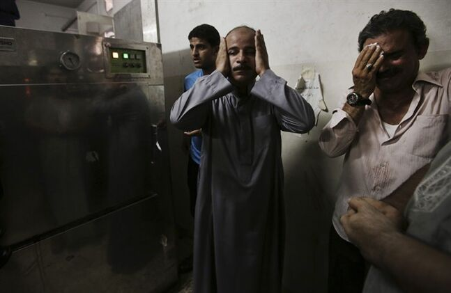 Palestinian relatives mourn in the morgue of Shifa hospital following an explosion killing 10 people Monday, nine of them children, in an explosion at park at Shati refugee camp, in the northern Gaza Strip, Monday, July 28, 2014. Israeli and Palestinian authorities traded blame over the attack and fighting in the Gaza war raged on despite a major Muslim holiday. (AP Photo/Adel Hana)
