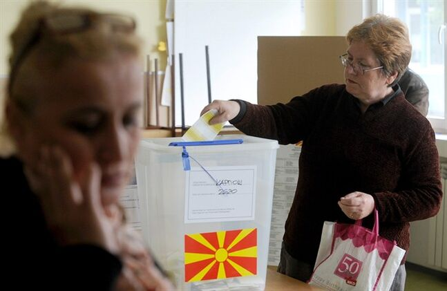 A woman cast her ballot for at a polling station in Skopje, Macedonia, Sunday, April 27, 2014. Macedonia votes Sunday in a presidential election runoff and snap parliamentary elections. (AP Photo/Boris Grdanoski)