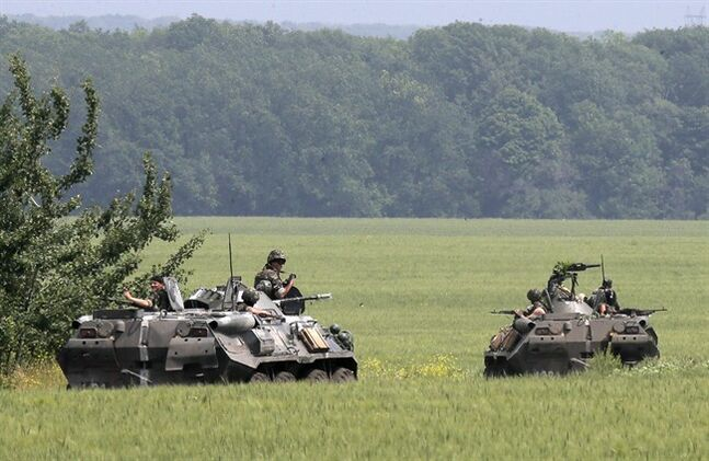 Members of the Ukrainian army inspect an area near Slovyansk, Ukraine, Friday, May 30, 2014. The Ukrainian Acting Defence Minister said on Friday that troops had ousted separatists from southern and western parts of the Donetsk region and north of the Luhansk region. (AP Photo/Efrem Lukatsky)