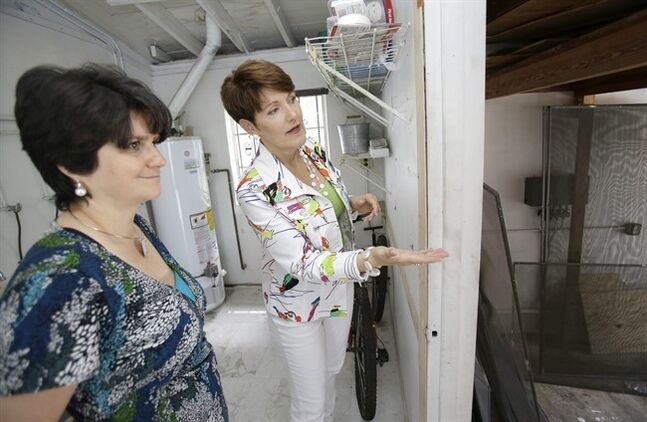 In this Thursday, May 29, 2014 photo, real estate broker Nancy Dowson, right, with Keller Williams Realty, shows a house to prospective buyer Mary Tuttle, in Miami Shores, Fla. The National Association of Realtors reports on existing-home sales in May on Monday, June 23, 2014. (AP Photo/Wilfredo Lee)