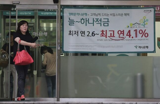 A woman walks past an advertisement for a bank's interest rate in Seoul, South Korea, Thursday, Aug. 14, 2014. South Korea's central bank, Bank of Korea, cut its key interest rate for the first time in 15 months on Thursday, providing support to an economy dragged down by the shock of a ferry sinking that killed hundreds of teenagers. The banner reads: