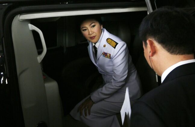 Thailand's Prime Minister Yingluck Shinawatra is leaving in her car after a meeting with election commissioners at the Army Club, Tuesday, Jan. 28, 2014, in Bangkok, Thailand. Thailand's government announced Tuesday it will go ahead with an election this weekend despite months of street protests and an opposition boycott. (AP Photo/Wally Santana)