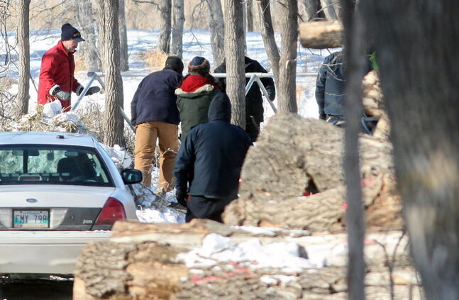 Workers and Brandon Police Service members erect a tent near the banks of the Assiniboine River in Queen Elizabeth Park on Wednesday afternoon.