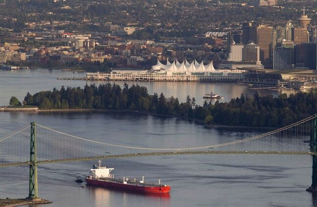 A oil tanker is guided by tug boats as it goes under the Lions Gate Bridge at the mouth of Vancouver Harbour on May 5, 2012. THE CANADIAN PRESS/Jonathan Hayward
