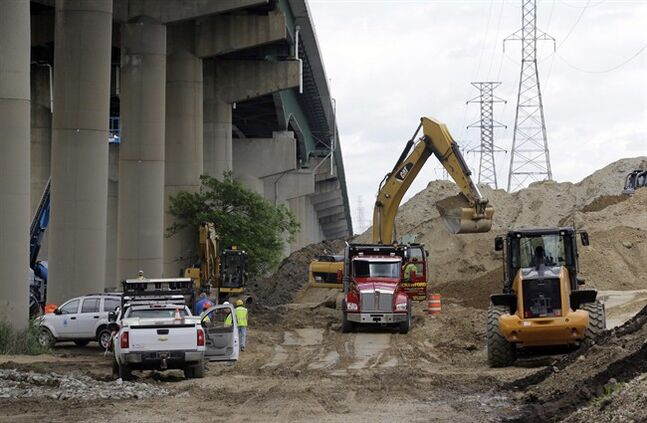 Workers remove a pile of dirt next to the Interstate 495 bridge over the Christina River near Wilmington, Del., June 5, 2014. THE CANADIAN PRESS/AP, Patrick Semansky