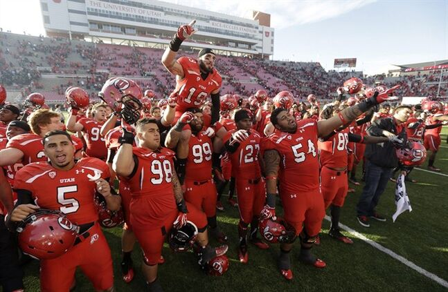 FILE - In this Nov. 30, 2013, file photo, Utah players celebrate at the end of their NCAA college football game against Colorado, in Salt Lake City. University of Utah President David Pershing says he agrees it's time to consider some changes to the school fight song that some find sexist. Pershing announced Monday, May 5, 2014, he's asking the Office of Student Affairs to oversee a committee that will weigh a