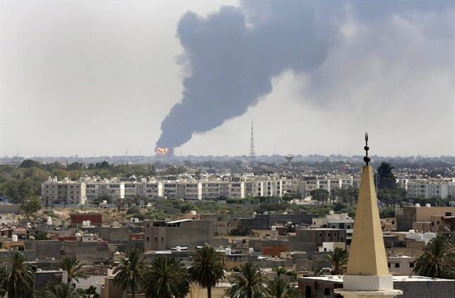 Black smoke billows over the skyline as a fire at the oil depot for the airport rages out of control after being struck in the crossfire of warring militias battling for control of the airfield, in Tripoli, Libya Monday, July 28, 2014. The latest violence to plague the country has so far killed scores of people and wounded hundreds as foreigners flee the chaos. Libya's interim government said in a statement that the fire could trigger a