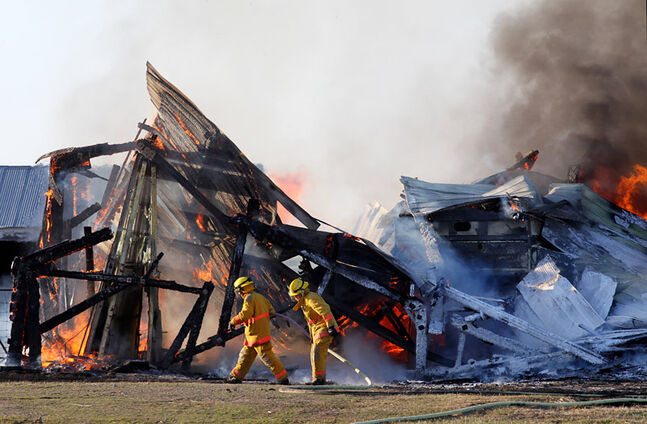 Firefighters with the Souris Fire Department battle a blaze that destroyed a barn north of Souris on Friday evening. No one was injured in the blaze that destroyed some farm equipment in addition to the building.