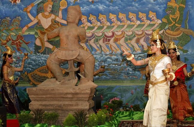 Cambodian dancers perform a blessing dance near the three pieces of the 10th century Cambodian sandstone statues from the United States, during a handover ceremony at the Council of Ministers, in Phnom Penh, Cambodia, Tuesday, June 3, 2014. Three 1,000-year-old statues depicting Hindu mythology were welcomed home to Cambodia on Tuesday after being looted from a temple during the country's civil war and put in Western art collections. (AP Photo/Heng Sinith)